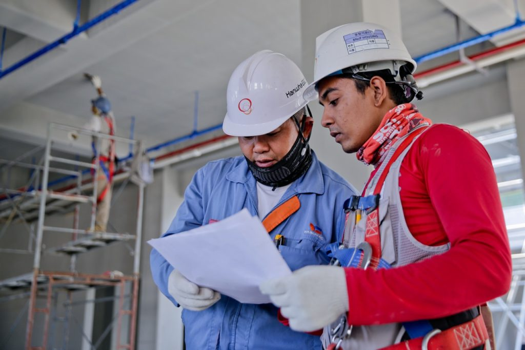 two construction man holding white paper